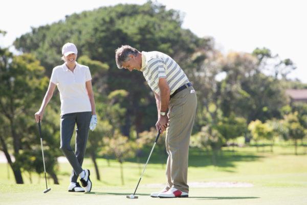 Golfers putting on green
