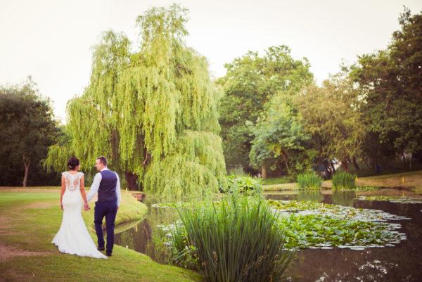 Bride & Groom walk by the lake